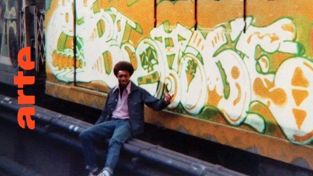 """Die 70er Jahre sind ohne Frage das goldene Zeitalter des New Yorker Subway-Graffitis. Keiner prägt diese Zeit so wie BLADE, LEE und SEEN, die seitdem einen festen Platz im Graffiti-Olymp haben. Anstatt sich in Gang-Kriegen auf der Straße herumzutreiben, wollen die """"Graffiti-Kings"""" in den 70ern nur eins: Ihren Namen auf so vielen vorbeirauschende Züge wie möglich schreiben. Und dafür gehen sie jedes Risiko ein - ganz nach dem Motto: """"Go big or go home!"""" Hauptsache, das nächste Writing wird noch größer und verrückter als das letzte. Mit Hip-Hop Kultur hat Graffiti damals noch nicht viel zu tun. BLADE und COMET hören den Soundtrack von """"Forrest Gump"""", wenn sie nachts ihre Pieces malen. Erst als Graffiti als Hip-Hop Kultur verpackt nach Europa kommt, wird DJing und Breakdance plötzlich zum festen Bestandteil der Writing-Kultur. Die nächste Folge gibt's am Mittwoch um 18 Uhr: The Rise of Graffiti Writing S2 - Style Wars // SEEN The Rise of Graffiti Writing """"The Rise of Graffiti Writing"""" zeichnet die Geschichte der Graffiti-Kultur von den Anfängen im New York der 70er bis zum Ausbruch des Lack-Virus' Mitte der 80er in Europa nach. Writer der ersten Stunde erzählen, wie die Bewegung in den 80er-Jahren von den USA über den großen Teich nach Europa schwappte und sich ab 1983 von Amsterdam, Paris und London oder der heimlichen Graffiti-Metropole Kopenhagen in ihren Bann zog."""