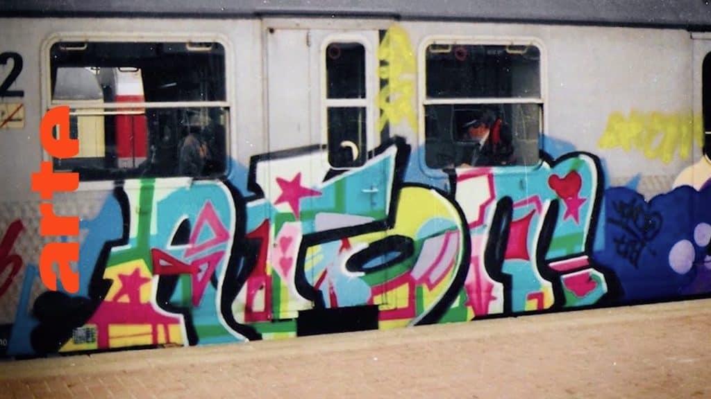 """Graffiti-Writer Bomber aus Frankfurt und Shark aus Dortmund gehören zu den Urgesteinen der deutschen Szene. Dortmund wurde Mitte der Achtziger Jahre zur Graffiti-Hochburg im Ruhrgebiet und lieferte wichtige Impulse für Entwicklungen in anderen großen Städten, traf aber nicht nur auf Begeisterung seitens der Einwohner. The Rise of Graffiti Writing """"The Rise of Graffiti Writing"""" zeichnet die Geschichte der Graffiti-Kultur von den Anfängen im New York der 70er bis zum Ausbruch des Lack-Virus' Mitte der 80er in Europa nach. Writer der ersten Stunde erzählen, wie die Bewegung in den 80er-Jahren von den USA über den großen Teich nach Europa schwappte und sich ab 1983 von Amsterdam, Paris und London oder der heimlichen Graffiti-Metropole Kopenhagen in ihren Bann zog."""