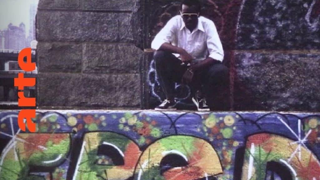 """Anfang der 1980er: Graffiti wird groß. Grund dafür ist auch der Undergroundfilm """"Wild Style!"""" (1982), heutzutage ein Klassiker und Symbol der neuen Kultur. Wir treffen seinen Macher Charlie Ahearn sowie LEE, den Hauptdarsteller des Films. Und was eine deutsche Fernsehanstalt mit """"Wild Style!"""" zu tun hat, erklärt uns Fab5Freddy, Hip-Hop-Pionier und Sprüher. In 10 Episoden zeichnet die Dokuserie den Aufstieg der Graffiti-Bewegung nach: vom New York der 70er über Amsterdam und Paris bis nach München, von wo aus der Graffitivirus ab den 80ern ganz Europa infizierte. The Rise of Graffiti Writing """"The Rise of Graffiti Writing"""" zeichnet die Geschichte der Graffiti-Kultur von den Anfängen im New York der 70er bis zum Ausbruch des Lack-Virus' Mitte der 80er in Europa nach. Writer der ersten Stunde erzählen, wie die Bewegung in den 80er-Jahren von den USA über den großen Teich nach Europa schwappte und sich ab 1983 von Amsterdam, Paris und London oder der heimlichen Graffiti-Metropole Kopenhagen in ihren Bann zog."""