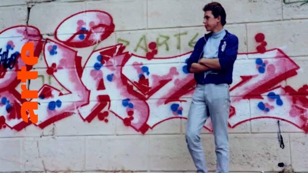 """Ein Happening, von dem Graffiti-Jünger sagen: Das war ein fettes Ding. MODE2, SHOE und BANDO, Gründer der ersten europäischen Graffiti Crew Crime Time Kings, treffen sich in Amsterdam, um gemeinsam eine Wand zu malen. Über 30 Jahre nach den ersten Bildern legen sie die Style-Latte 2017 nochmal ziemlich hoch. Wir begleiten sie beim Skizzieren im Atelier und folgen ihnen zur Revival-Wand. In 10 Episoden zeichnet die Dokuserie den Aufstieg der Graffiti-Bewegung nach: vom New York der 70er über Amsterdam und Paris bis nach München, von wo aus der Graffitivirus ab den 80ern ganz Europa infizierte. The Rise of Graffiti Writing """"The Rise of Graffiti Writing"""" zeichnet die Geschichte der Graffiti-Kultur von den Anfängen im New York der 70er bis zum Ausbruch des Lack-Virus' Mitte der 80er in Europa nach. Writer der ersten Stunde erzählen, wie die Bewegung in den 80er-Jahren von den USA über den großen Teich nach Europa schwappte und sich ab 1983 von Amsterdam, Paris und London oder der heimlichen Graffiti-Metropole Kopenhagen in ihren Bann zog."""