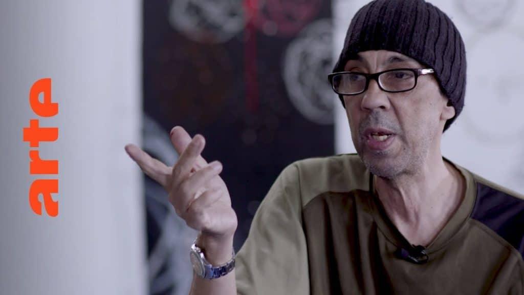 """NYC in den 1980ern: Graffiti startet durch. Keith Haring, Jean-Michel Basquiat und Co. eignen sich die Codes der Sprüher an – und tragen diese Kunst so von der Straße in die Galerien. Gleichzeitig nehmen The Clash und FUTURA2000 einen Song auf, der weitreichende Folgen für die Graffiti-Bewegung in Europa haben sollte: Das erste Piece entsteht in London. Sein Urheber Fute alias FUTURA2000 erzählt, wie Graffiti nach Großbritannien kam. In 10 Episoden zeichnet die Dokuserie den Aufstieg der Graffiti-Bewegung nach: vom New York der 70er über Amsterdam und Paris bis nach München, von wo aus der Graffitivirus ab den 80ern ganz Europa infizierte. The Rise of Graffiti Writing """"The Rise of Graffiti Writing"""" zeichnet die Geschichte der Graffiti-Kultur von den Anfängen im New York der 70er bis zum Ausbruch des Lack-Virus' Mitte der 80er in Europa nach. Writer der ersten Stunde erzählen, wie die Bewegung in den 80er-Jahren von den USA über den großen Teich nach Europa schwappte und sich ab 1983 von Amsterdam, Paris und London oder der heimlichen Graffiti-Metropole Kopenhagen in ihren Bann zog."""