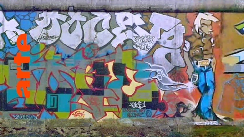 """Graffiti in Deutschland: Die Maler-Urgesteine STONE, NEON und LOOMIT sind die ersten ihres Fachs. Ab Mitte der 80er Jahre sorgen sie dafür, dass ihre Bilder unters Volk kommen – vorzugsweise auf Waggons der Deutschen Bahn. Aus heutiger Sicht kaum zu glauben: All das passierte nicht in Berlin, sondern in und um München. In dieser Episode erfahren wir, was es mit dem Geltendorfer Zug auf sich hatte und wie Graffiti den Weg in die restliche BRD fand. In 10 Episoden zeichnet die Dokuserie den Aufstieg der Graffiti-Bewegung nach: vom New York der 70er über Amsterdam und Paris bis nach München, von wo aus der Graffitivirus ab den 80ern ganz Europa infizierte. The Rise of Graffiti Writing """"The Rise of Graffiti Writing"""" zeichnet die Geschichte der Graffiti-Kultur von den Anfängen im New York der 70er bis zum Ausbruch des Lack-Virus' Mitte der 80er in Europa nach. Writer der ersten Stunde erzählen, wie die Bewegung in den 80er-Jahren von den USA über den großen Teich nach Europa schwappte und sich ab 1983 von Amsterdam, Paris und London oder der heimlichen Graffiti-Metropole Kopenhagen in ihren Bann zog."""
