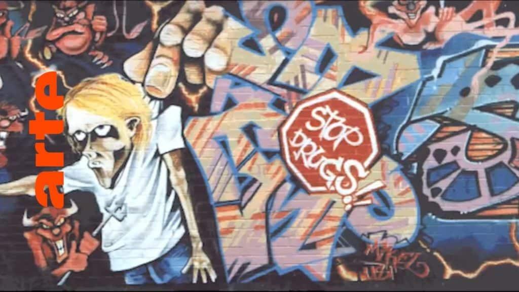 """Graffiti in Deutschland, Teil 2: Von München über Dortmund geht's nach Hamburg, wo wir HESH, DAIM und JBK treffen, alle drei Writer der ersten Stunde. Sie sprechen über ihren ersten Kontakt mit der Graffitikultur und berichten von der Stylespritze, die ihnen der Pariser King BANDO verabreichte. In 10 Episoden zeichnet die Dokuserie den Aufstieg der Graffiti-Bewegung nach: vom New York der 70er über Amsterdam und Paris bis nach München, von wo aus der Graffitivirus ab den 80ern ganz Europa infizierte. In der letzten Episode unserer Dokuserie heißt es: Graffiti in Deutschland, In 10 Episoden zeichnet die Dokuserie den Aufstieg der Graffiti-Bewegung nach: vom New York der 70er über Amsterdam und Paris bis nach München, von wo aus der Graffitivirus ab den 80ern ganz Europa infizierte. The Rise of Graffiti Writing """"The Rise of Graffiti Writing"""" zeichnet die Geschichte der Graffiti-Kultur von den Anfängen im New York der 70er bis zum Ausbruch des Lack-Virus' Mitte der 80er in Europa nach. Writer der ersten Stunde erzählen, wie die Bewegung in den 80er-Jahren von den USA über den großen Teich nach Europa schwappte und sich ab 1983 von Amsterdam, Paris und London oder der heimlichen Graffiti-Metropole Kopenhagen in ihren Bann zog."""