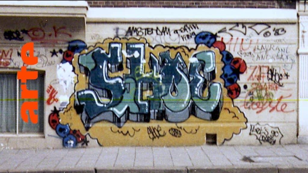 """MICKEY, die erste europäische Sprüherin, führt uns zu Yaki Kornblit. Anfang der 80er ging der Kunstsammler nach New York, wo er sich in die Werke von FUTURA2000, DONDI, SEEN und Co. verliebte. Ab 1983 stellt er sie in Amsterdam aus und macht Graffiti so salonfähig. Zur selben Zeit vermischt sich das New Yorker Stylewriting mit dem Punk-lastigen Tagging-Style Amsterdamer Schule. Writer der ersten Stunde wie DELTA und SHOE erzählen. In 10 Episoden zeichnet die Dokuserie den Aufstieg der Graffiti-Bewegung nach: vom New York der 70er über Amsterdam und Paris bis nach München, von wo aus der Graffitivirus ab den 80ern ganz Europa infizierte. The Rise of Graffiti Writing """"The Rise of Graffiti Writing"""" zeichnet die Geschichte der Graffiti-Kultur von den Anfängen im New York der 70er bis zum Ausbruch des Lack-Virus' Mitte der 80er in Europa nach. Writer der ersten Stunde erzählen, wie die Bewegung in den 80er-Jahren von den USA über den großen Teich nach Europa schwappte und sich ab 1983 von Amsterdam, Paris und London oder der heimlichen Graffiti-Metropole Kopenhagen in ihren Bann zog."""